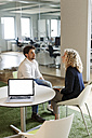 Two colleagues talking in office with laptop on table - PESF00662