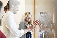 Smiling colleagues in office at glass pane with adhesive notes - PESF00671