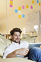 Smiling man in office using tablet in bean bag - PESF00674