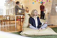 Woman doing yoga in bean bag with meeting in background - PESF00680