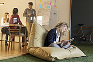 Woman in office using tablet in bean bag with meeting in background - PESF00683