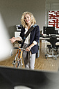 Smiling woman with bicycle in office - PESF00686