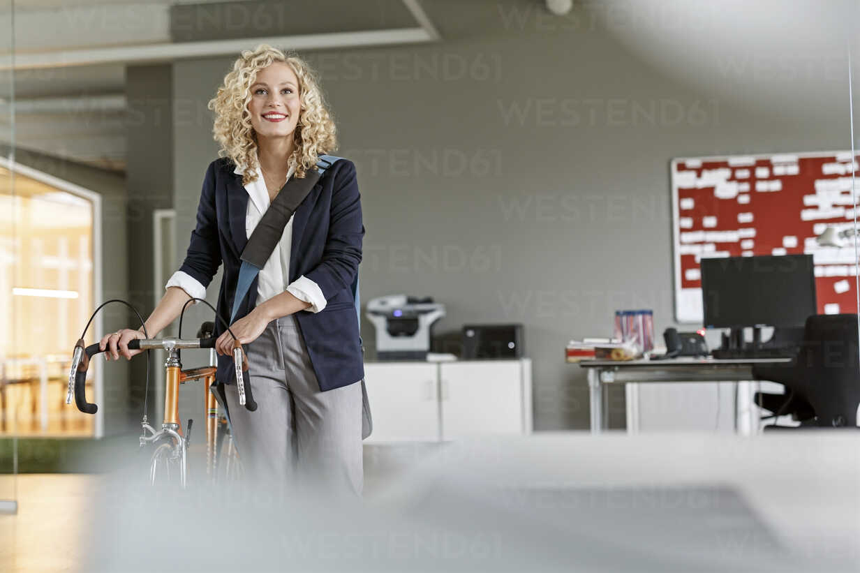 Smiling woman with bicycle in office - PESF00689 - Peter Scholl/Westend61