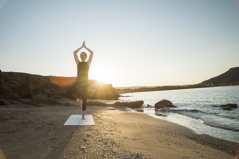 Greece, Crete, woman practicing yoga on the beach at sunset - CHPF00406