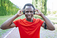 Portrait of man in sportswear listening  music with headphones - KIJF01563