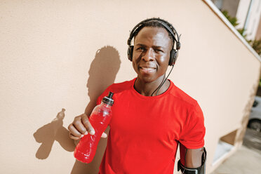 Portrait of man with isotonic drink in sportswear listening music with headphones - KIJF01575