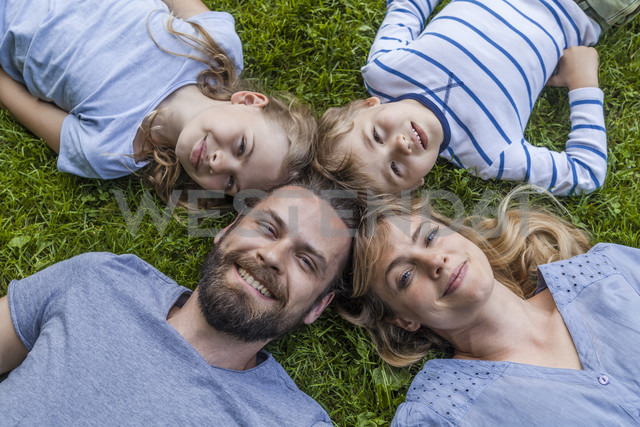 Portrait of happy family lying in meadow - TCF05437
