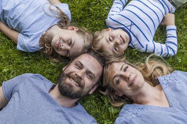 Portrait of happy family lying in meadow - TCF05437
