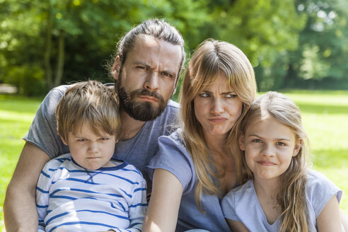 Portrait of playful family pulling faces outdoors - TCF05443