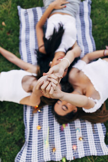 Friends in a park lying on blanket raising their arms - JPF00227