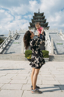 South Korea, Seoul, woman holding a baby girl in front of the National Folk Museum of Korea, inside Gyeongbokgung Palace - GEMF01689