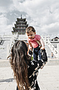South Korea, Seoul, woman holding a baby girl in front of the National Folk Museum of Korea, inside Gyeongbokgung Palace - GEMF01692