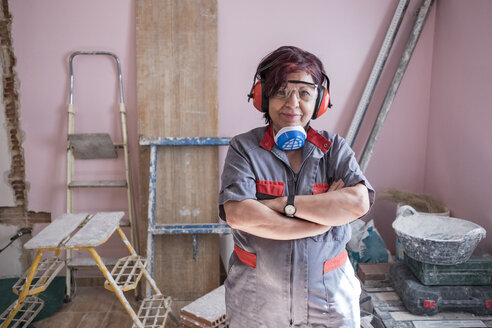 Portrait of senior woman with ear protection and respirator at construction site - JASF01786