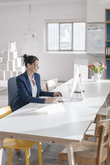 Businesswoman working at desk in a loft - JOSF01159