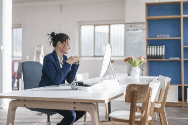 Businesswoman sitting at desk in a loft drinking coffee - JOSF01162