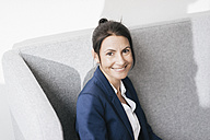Portrait of smiling businesswoman on a couch - JOSF01168
