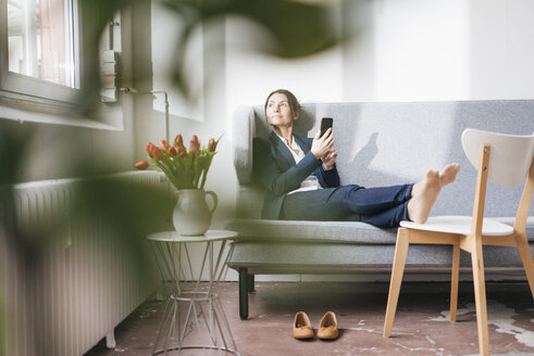 Businesswoman sitting on couch in a loft looking out of the window - JOSF01171