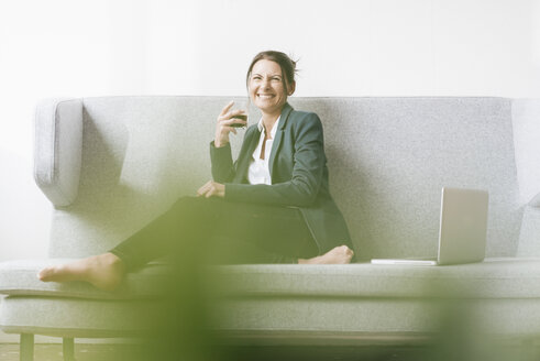 Portrait of laughing businesswoman relaxing on a couch - JOSF01174