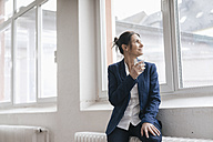 Businesswoman with glass of water sitting on radiator in a loft looking through window - JOSF01177