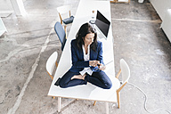 Businesswoman sitting on desk in a loft using tablet - JOSF01186