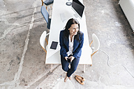 Smiling businesswoman sitting on desk in a loft - JOSF01189