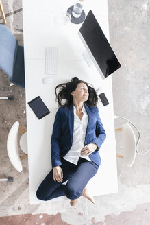 Businesswoman lying on desk in the office - JOSF01192