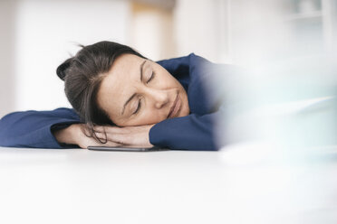 Overworked woman sleeping on desk in office - JOSF01207