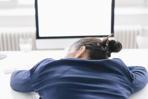 Back view of overworked woman sleeping on desk in office - JOSF01213
