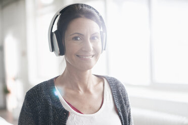 Portrait of smiling woman listening music with headphones in front of a window - JOSF01216