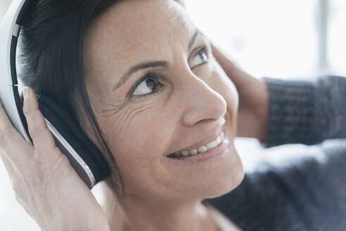 Portrait of smiling woman listening music with headphones - JOSF01219