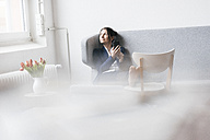 Businesswoman sitting on couch in a loft looking out of the window - JOSF01234