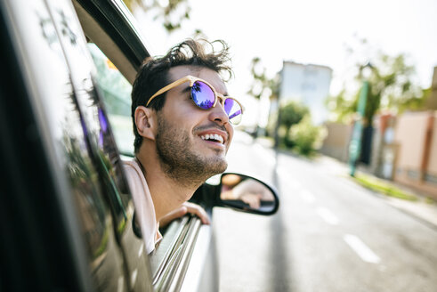 Man with sunglasses leaning out the window of a car in motion - KIJF01588