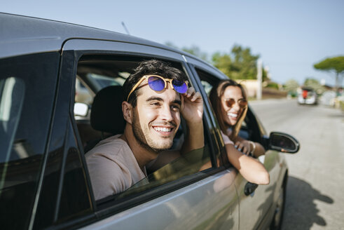 Happy young man and woman in a car looking out the window - KIJF01594