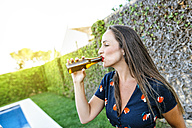 Young woman drinking beer at the poolside - KIJF01618
