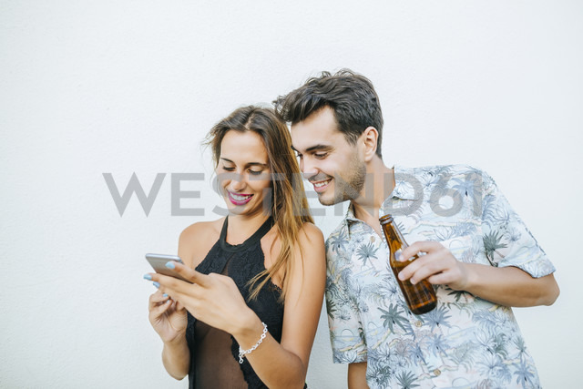 Young couple with beer and cell phone outdoors - KIJF01621 - Kiko Jimenez/Westend61