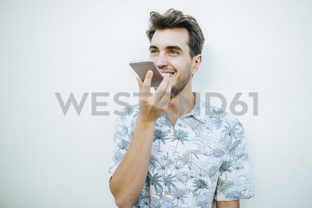 Man using cell phone in front of white wall - KIJF01624 - Kiko Jimenez/Westend61