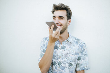 Man using cell phone in front of white wall - KIJF01624