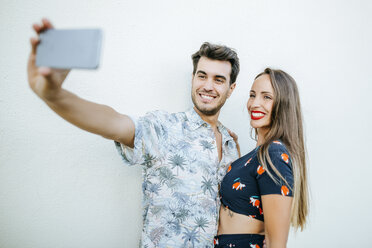 Couple taking a selfie with smartphone in front of white wall - KIJF01627