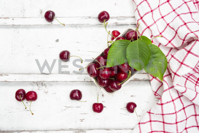 Cardboard box of cherries, leaves and kitchen towel on white wood - LVF06162