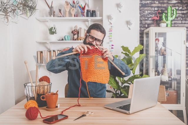 Bearded man knitting at home using laptop for watching online tutorial - RTBF00904 - Retales Botijero/Westend61