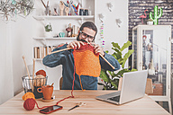 Bearded man knitting at home using laptop for watching online tutorial - RTBF00904