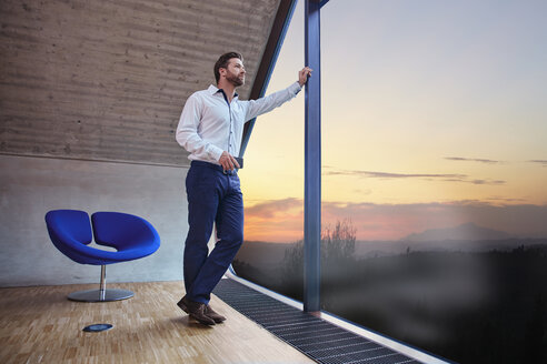 Businessman in attic office looking out of window at sunset - RHF01939