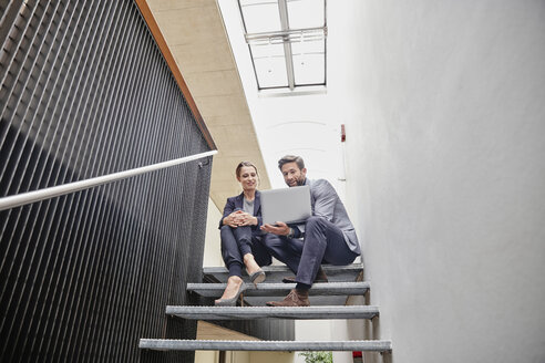 Businessman and businesswoman sitting on stairs in office sharing laptop - RHF01960