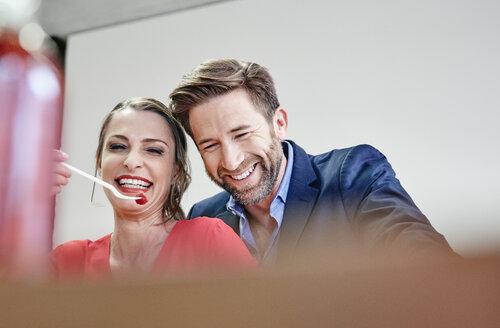Playful man and woman sharing a raspberry - RHF01978