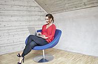 Businesswoman sitting in chairusing laptop - RHF01993