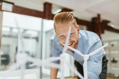 Businessman in office looking at models of wind turbines - ZEDF00602
