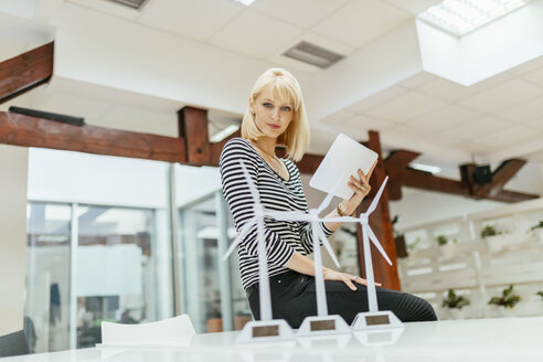 Businesswoman in office looking at models of wind turbines - ZEDF00605