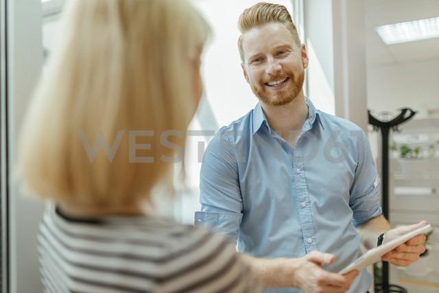 Businessman and woman standing in corridor, talking - ZEDF00617
