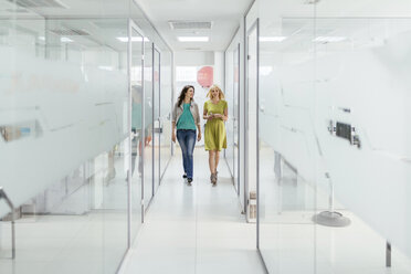 Two female colleagues walking in office corridor - ZEDF00644