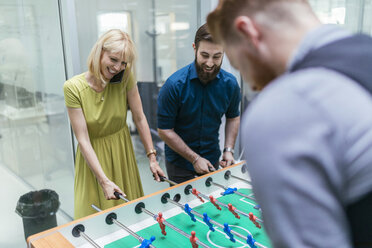 Colleagues playing foosball in office - ZEDF00647